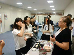 ふかひれラーメンを試食した中国と香港の留学生と商品説明する丸光の敬子専務。